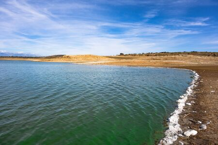 Valdecañas Reservoir, Caceres, Spain, shore contaminated with white foam and green water due to pollution and dead algae