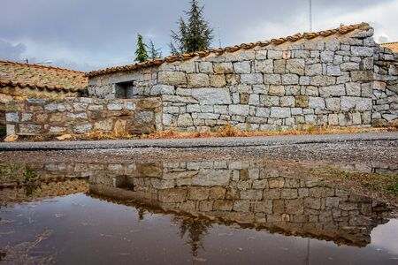 Old house in the village and its reflection in a puddle