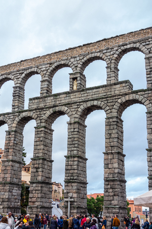 Segovia, Spain; 01112019: Segovia aqueduct on a cloudy day with people below