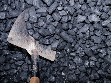 Metal shovel with wooden handle collecting carbon stones from a pile Stock fotó