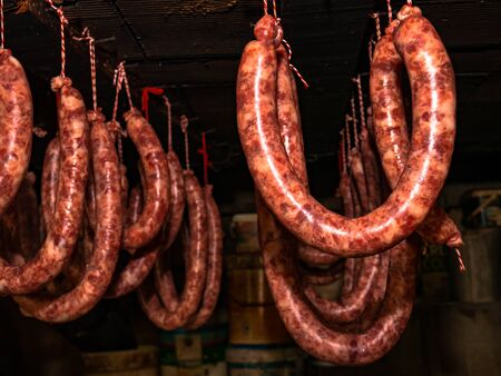 Sausage horseshoes hanging from the ceiling with ropes to proceed to the smoked sausage Reklamní fotografie
