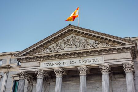 Madrid, Spain; 06/12/2019: Gable of the facade of the congress building of the deputies of Spain, where the representatives elected by the Spanish people work, topped by a Spanish flag