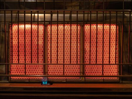 Front panel of a butane stove lit with the panel in red incandescent and the blue flame of the ignition