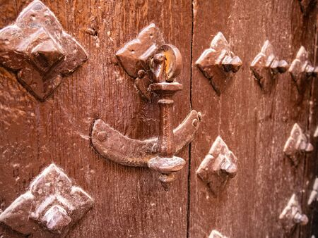 Metal knocker on an old wooden door and surrounded by deterrent skewers