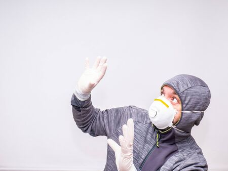 Man with mask and gloves looks surprised up