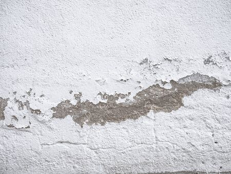 White wall deteriorated by the passage of time with stains due to lack of paint