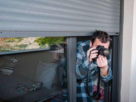 Misaligned man in checkered robe taking photos from his home terrace hidden under the blind during confinement due to coronavirus alertness