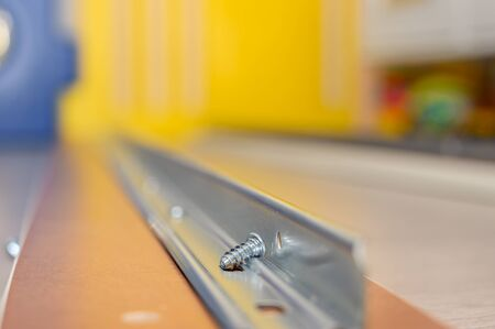 Macro photography of a screw deposited on the rail in which it will be screwed Banque d'images