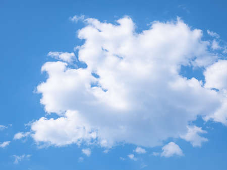 Large cloud formed in the sky surrounded by diffuse clouds and a blue sky in the background
