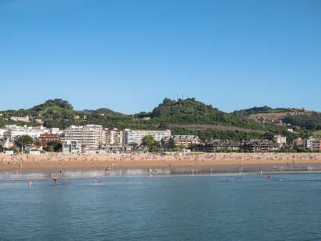 Laredo, Cantabria, Spain; 07 04 2020: View of La Salve beach in Laredo, Cantabria and the Pico del Hacha mountain in the background. Tourists and bathers enjoying a sunny day on the beach