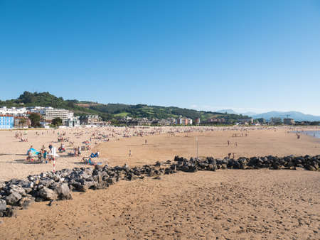Laredo, Cantabria, Spain; 07 04 2020: View of La Salve de Laredo beach and characteristic rocks as bathers and tourists enjoy a sunny day on vacation with a beautiful blue sky in the background