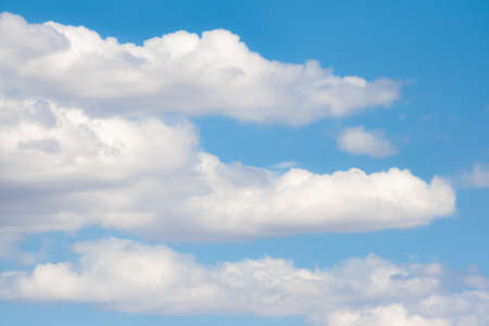 Three scattered cloud clusters with a nice blue sky in the background