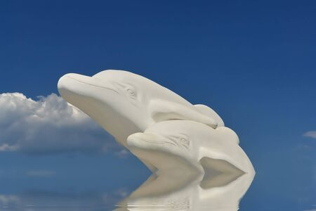 Two happy dolphins from white greek marble