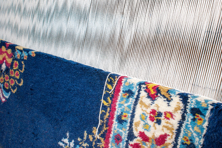 Partly woven carpet, rug on a loom shows wool pile, foundation, warp and weft Stock Photo