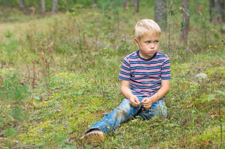 The boy in the woods sitting on moss  photo