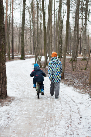 Children walk along a path in a park in winter. Stock Photo