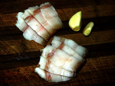 on a wooden chopping board are pieces of chopped lard and two cloves of garlic a top view