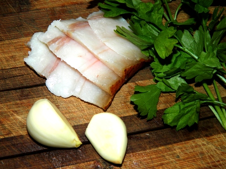 white washed: on a wooden chopping board are a branch of fresh parsley and two cloves of garlic and lard cut into chunks top view Stock Photo