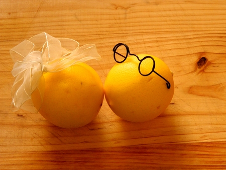 a meeting with a view to marriage: on light wood chopping board are a pair of lovers kissing and yellow lemons boy in dark glasses and a girl with a white bow on a horizontal surface with top view and front