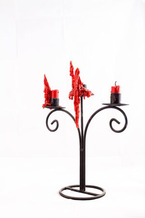 candelabrum: An iron stylized candle stand with three red candles melted and consumed Stock Photo