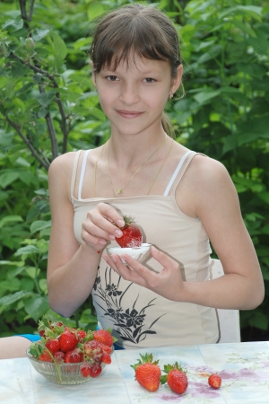 The girl sits at a table in the garden eating fresh strawberries with sugar