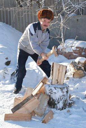 A man in a light jacket chopping wood for the stove in winter Cleaver bath