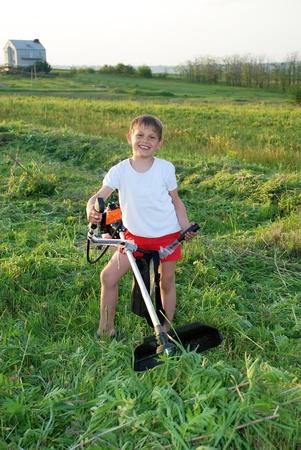 Junior benzokosoy mower with grass on the workpiece