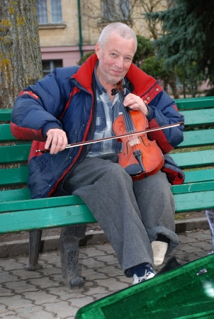 Street musician plays the violin on the bench of the Park earning a living
