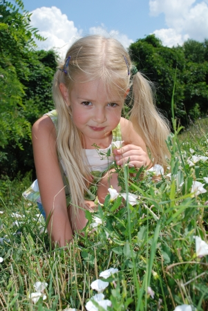 A girl sits on a summer day on the meadow with flowers Stock Photo