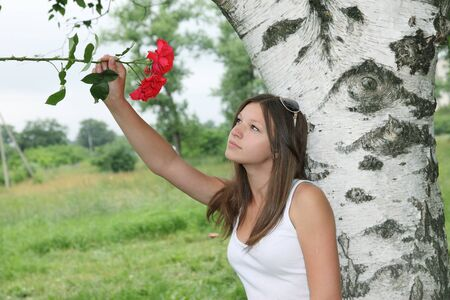 Portrait of a girl with red roses standing under a white birch