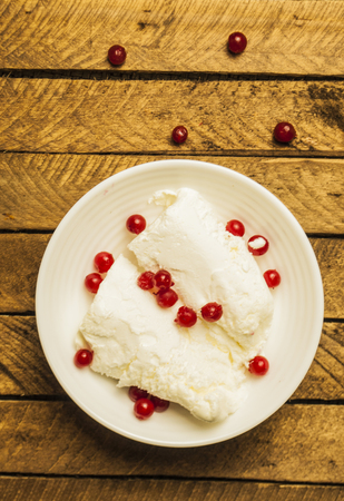 Ice cream with red, ripe raspberries in a white, rippled plate on a woody dark background
