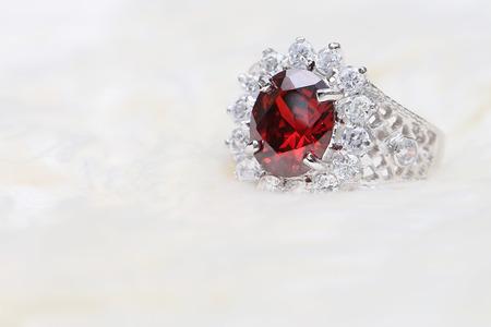red gemstone on diamond ring