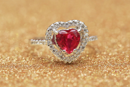 red gemstone on diamond ring