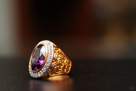 Purple gem stone on gold ring with diamond Foto de archivo