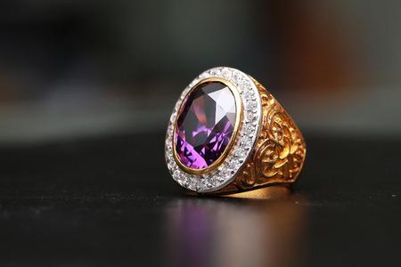 Purple gem stone on gold ring with diamond Archivio Fotografico