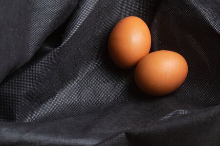 Eggs on black fabric background