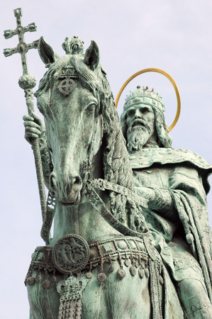 bl: A bronze statue of Stephen I of Hungary mounted on a horse, erected in 1906, can be seen between the Bastion and the Matthias Church. The pedestal was made by Alajos Stróbl, based on the plans of Frigyes Schulek, in Neo-Romanesque style, with episodes il