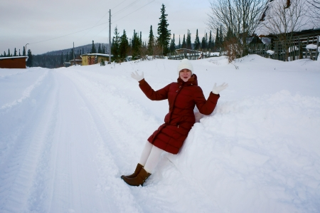 snowbanks: Girl sitting on the snowbank in a winter day  Stock Photo