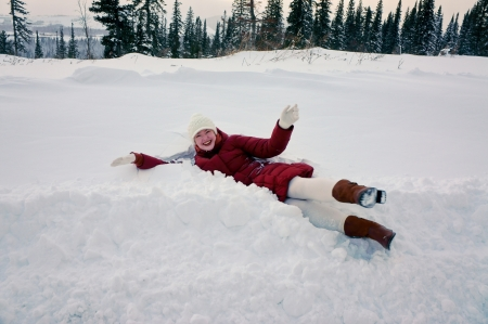 snowbank: Girl lying in the snowbank in a winter day