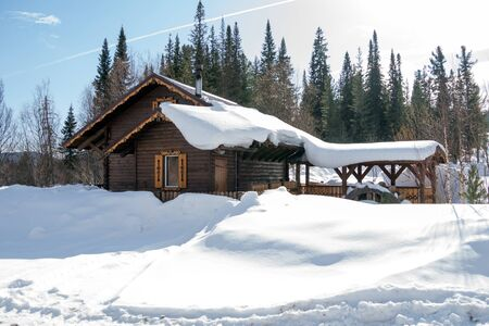 A wooden house stands among white snowdrifts against a background of spruce forest.