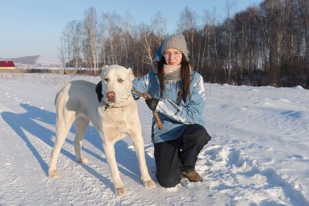 The girl sat down with a big white shepherd dog on the side of the road amid the forest. Imagens