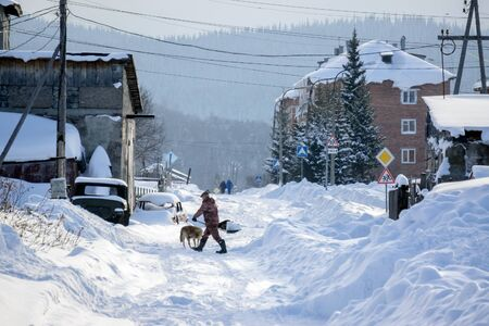 Man with a shovel cleans snow on the outskirts of the village on the background of residential buildings. Stock Photo