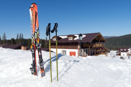 Alpine skiing with sticks stand in a white snowdrift against the background of the Swiss cottage. Stock Photo