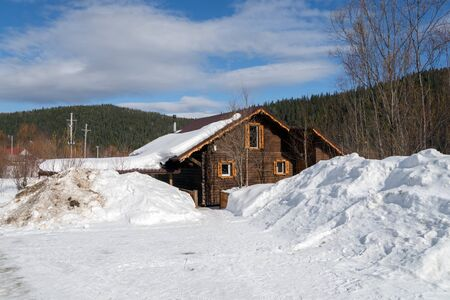 The snowy road leads to a wooden house among the snowdrifts against the background of the taiga. Stock Photo