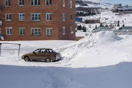 The car stands among the high snowdrifts in the courtyard of a residential building. Stock Photo