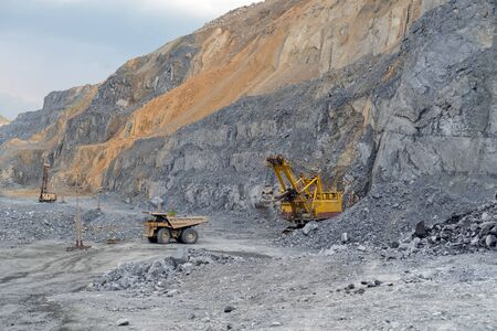 Dump truck Caterpillar loaded with nepheline ore pulls away from the excavator. 스톡 콘텐츠