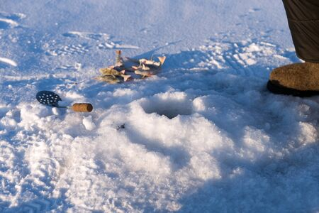 Perch and spoon for scooping ice are near the hole for catching fish, on the surface of a snow-covered lake.