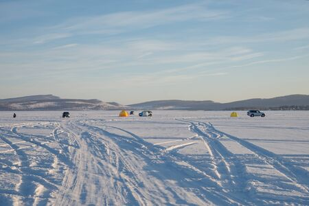 Car tracks lead to Fishermen who catch fish on the Great Frozen Lake, against the backdrop of the mountains, in winter.