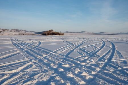 Car tracks go across the frozen Great Lake to the island against the backdrop of the village of Parnaya, Krasnoyarsk Territory. Russia.