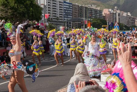 Colorful artists dance in front of the audience during the carnival. Santa Cruz de Tenerife. Spain